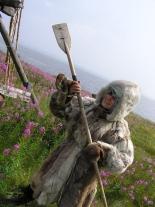 Зимняя меховая одежда и лыжная палка с лопаткой для установки капканов (демонстрирует участница экспедиции студентка РГГУ Лена Карвовская)